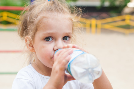 three year old: Three year old girl drinks from a bottle at the playground