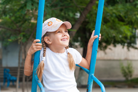 five year old: Happy five year old girl riding on a swing at the playground