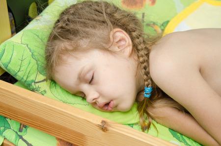 cansancio: Cinco a�os de la muchacha europeos dulcemente dormido en la cama