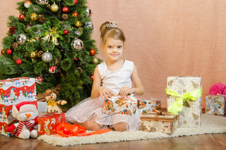 baby open present: Five-year girl in a New Years dress sitting on a mat at the Christmas tree Stock Photo