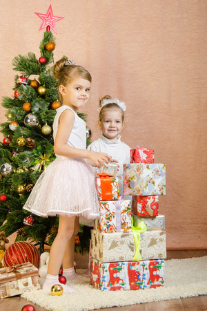 baby open present: Five-year and three-year girl in a New Years dress sitting on a mat at the Christmas tree