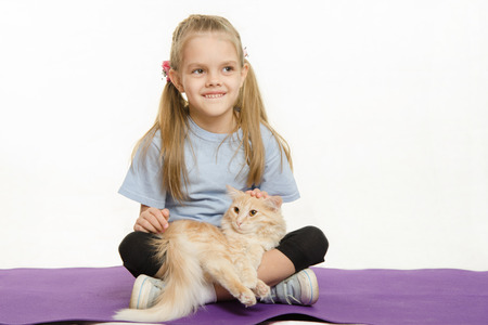 six year old: Six year old girl Europeans after exercise sitting on a rug with a domestic cat