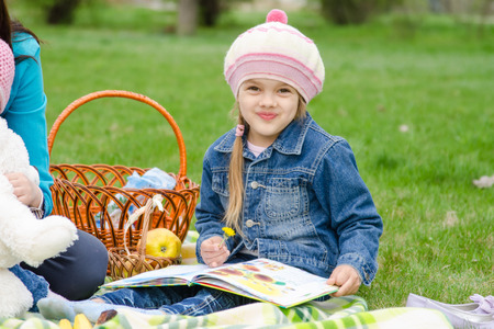 book jacket: A girl of five years in a denim jacket on a green lawn at a picnic with a book in their hands Stock Photo