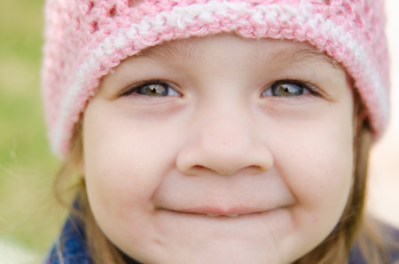 interesting: Close-up of a three-year girl with a cheerful smile in a pink hat