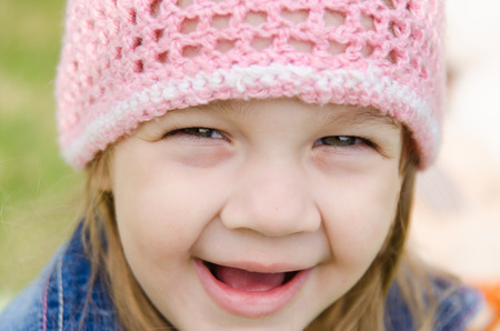 pink hat: Close-up of a three-year girl with a cheerful smile in a pink hat