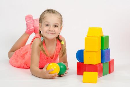 juguetes antiguos: Ni�a de cuatro a�os que juega en un cubos de estilo europeo, aislado en un fondo claro