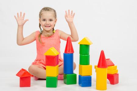 Niña de cuatro años que juega en un cubos de estilo europeo, aislado en un fondo claro