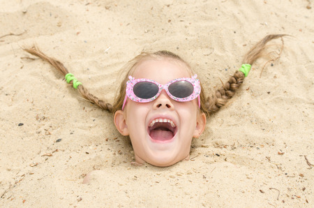 head in the sand: Funny five-year girl with glasses on a beach strewn on his head in the sand
