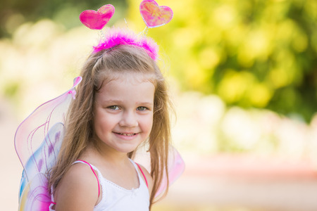 the antennae: happy four-year-girl in a fairy dress with wings on his back and antennae on his head Stock Photo