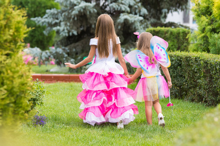 girl magic wand: Two little girls, princess and fairy strolling through the garden