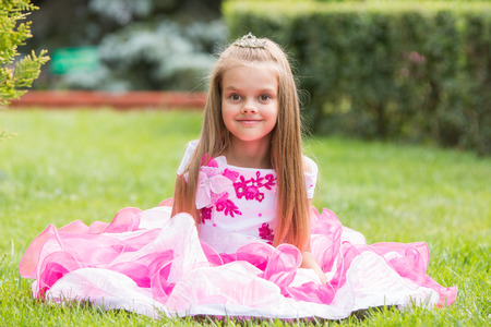 six year old: Happy six year old girl in a lush evening pink dress walking through the green garden
