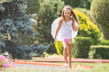 Happy six year old girl dressed as an angel with wings is walking with splashes of water for watering the lawn