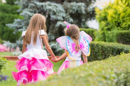 girl magic wand: Two girls of four and six years of walking through the green garden Stock Photo