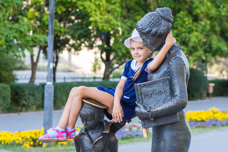 climbed: The girl sat comfortably on the monument to the first teacher Stock Photo