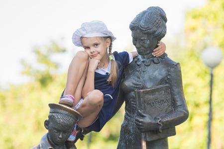 first year student: Girl climbs first teacher sculpture located in the Krasnoarmeysk district of Volgograd Boulevard Engels Stock Photo