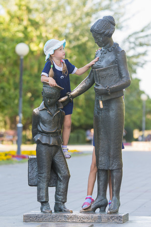 first year student: Girl climbs first teacher sculpture located in the Krasnoarmeysk district of Volgograd Boulevard Engels Stock Photo