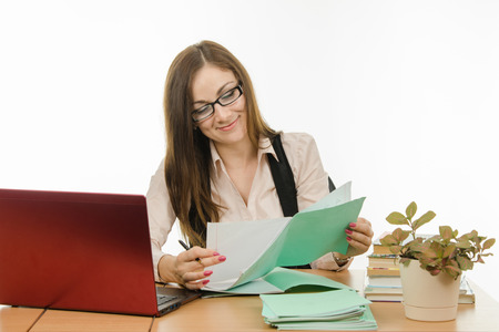 evaluating: Cute little girl is a teacher sitting at a desk with a laptop, books and notebooks