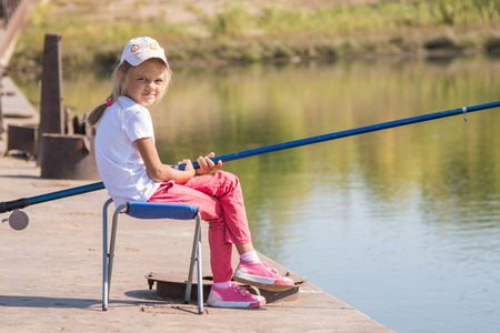 six year old: Six year old girl fishing from a bridge on a clear sunny day Stock Photo