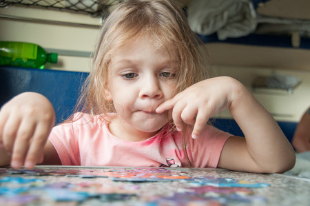 enthusiastically: The three-year girl enthusiastically collects puzzles reserved seats at a table in a train