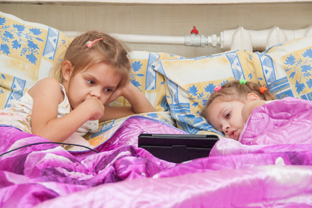 woman lying in bed: Two girls of three and five years, lie in bed and watch cartoons in the Tablet PC Stock Photo