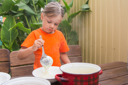 reluctant: Four-year girl on breakfast imposes a ladle into a bowl semolina Stock Photo