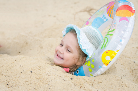 head in the sand: Four-year girl buried in the sand on the beach with his head planted under Circle