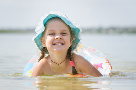 laps: Four-year girl with the Europeans bathed swimming laps in the river Stock Photo