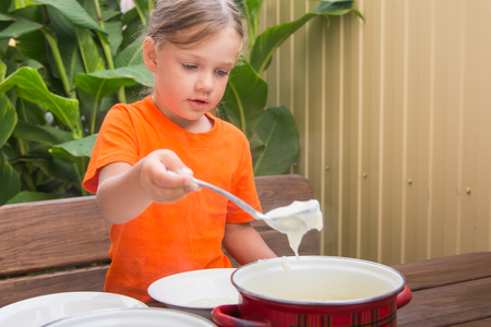 awakened: Four-year girl on breakfast imposes a ladle into a bowl semolina Stock Photo