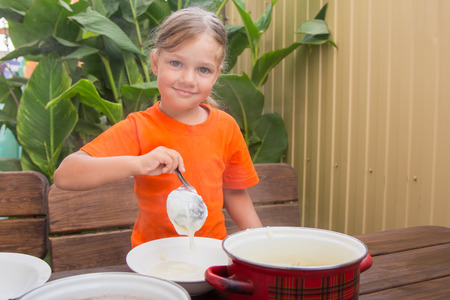 reluctant: Girl with a smile imposes semolina his plate