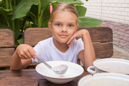 reluctant: Six year old girl at breakfast imposes a ladle into a bowl buckwheat Stock Photo