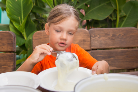 reluctant: The girl lays on breakfast porridge Stock Photo