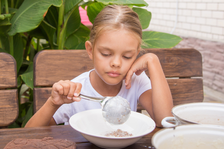awakened: Six year old girl at breakfast imposes a ladle into a bowl buckwheat Stock Photo