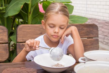 obudził: Six year old girl at breakfast imposes a ladle into a bowl buckwheat Zdjęcie Seryjne