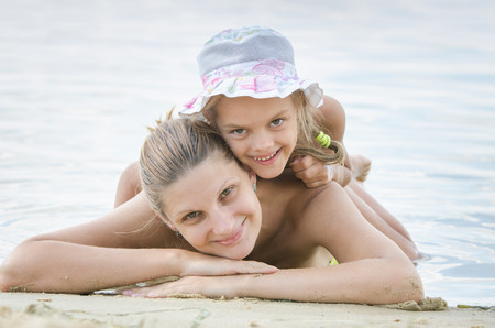 six year old: Six year old girl and a twenty-five woman lying on her stomach on the sand by the river Stock Photo