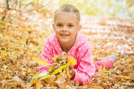 six year old: Six year old girl lying on the yellow fallen leaves Stock Photo