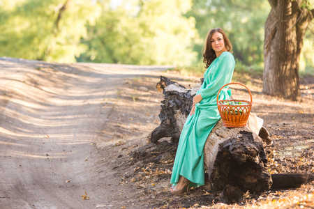 Young beautiful girl in a long dress walking in the woods on a warm summer day