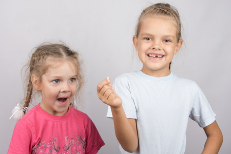 surprised baby: Six year old girl showing her the other girl had fallen Milk front upper teeth