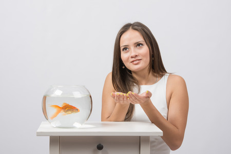 lustful: A young girl sits next to a round aquarium in which swimming goldfish