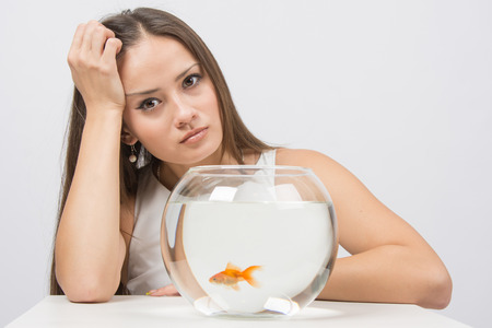 bad girl: A young girl sits next to a round aquarium in which swimming goldfish