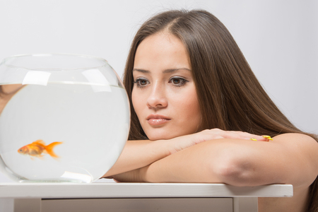 cherished: A young girl sits next to a round aquarium in which swimming goldfish