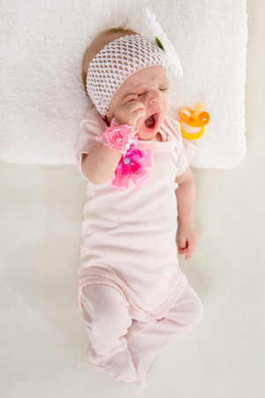 teat: a two-month baby girl Europeans lies on his back with a bandage on his head with a flower