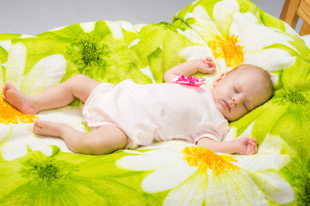 coverlet: a two-month baby girl Europeans lies on a soft bed on colored coverlet
