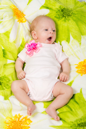 coverlet: a two-month baby girl lying on the bed Europeans on colored coverlet