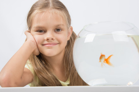 six year old: Happy six year old girl sits at a table at the fishbowl with goldfish