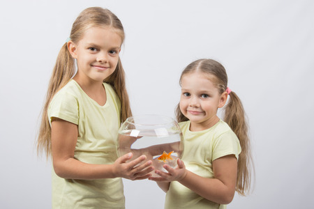 4 5 year old: Two happy girls four and six years are holding fishbowl with goldfish