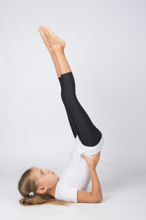 fulfill: six year old girl aspiring gymnast performs a number of training exercises Stock Photo