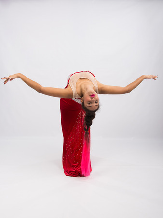 mulatto: Mulatto girl dancer performs a dance elements, isolated on a light background Stock Photo