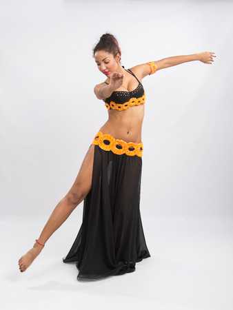 mulatto: Young girl mulatto dancing in a long black candid open dress, is isolated on a light background Stock Photo