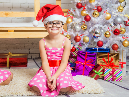 funny glasses: Girl in the red hat and the funny round glasses sits on the mat at the Christmas trees