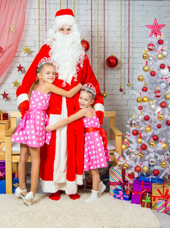 'grandfather frost': Children hugging grandfather frost from Christmas trees